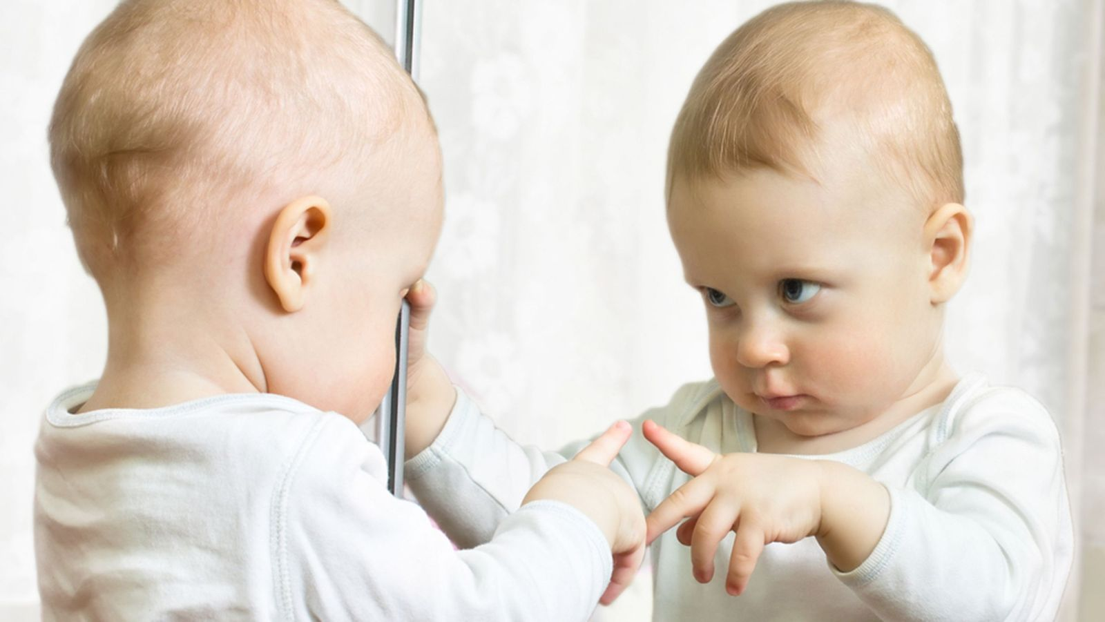 Ten month boy stands before the mirror; Shutterstock ID 129088694; PO: today-parents